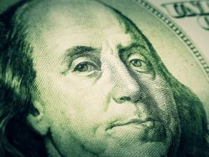 Smiling Benjamin Franklin portrait on a dollar bill.